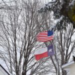 USA and Texas flags in the wind and snow